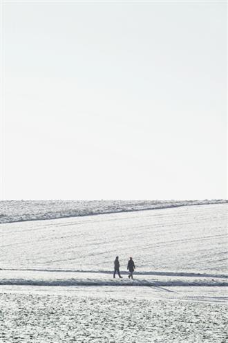 Paar spaziert über schneebedeckte Felder