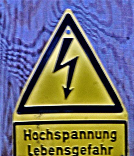 Warnschild an einem Strommast
